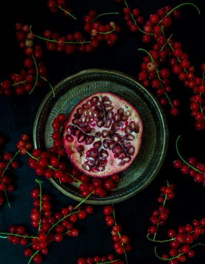 Stilleben rote Beeren mit Granatapfel